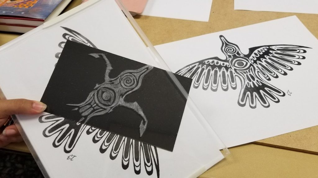 black and white work in progress, Haida-style raven being etched into plexiglass