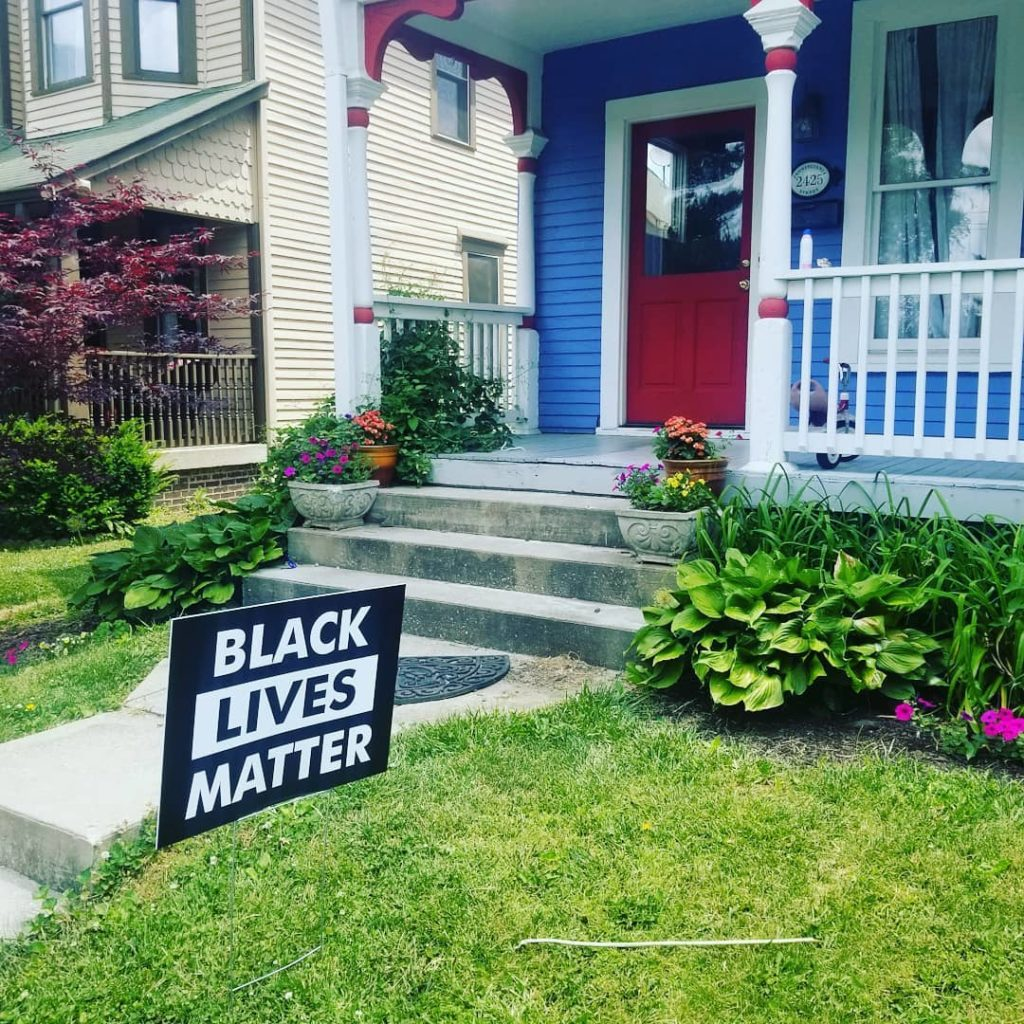 the front yard of a brightly-painted house with a verdant garden, sloppy grass, and a Black Lives Matter sign, on a sunny day